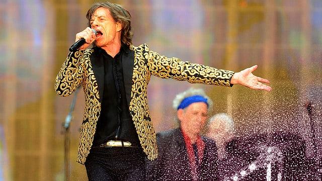 Mick Jagger trägt ein goldenes Jackett und sing in sein Mikrophon.
