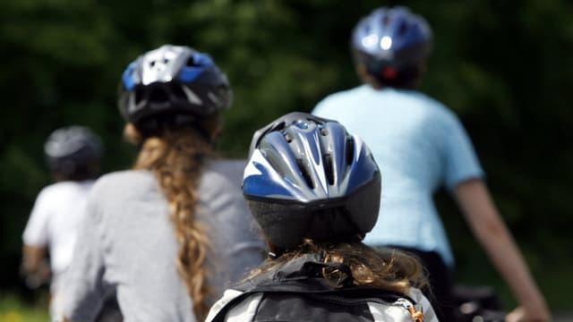 Drei Velofahrer mit Helm von hinten aufgenommen.