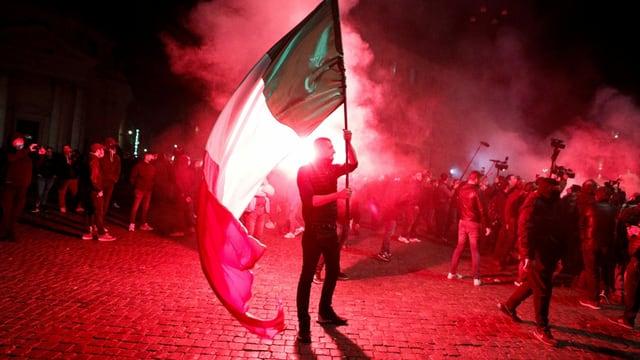 Protestierende mit Italien-Fahnen im Schein von roten Signalfackeln.