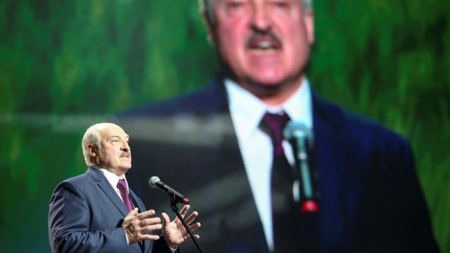 Lukaschenko spricht in ein Mikrofon, hinter ihm ist eine grosse Projektion von ihm zu sehen.