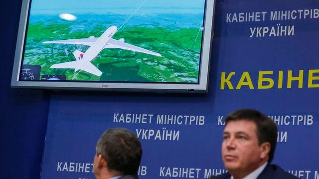 Zwei Männer sitzen vor einem Bildschirm, auf dem ein Flugzeugflug simuliert wird.