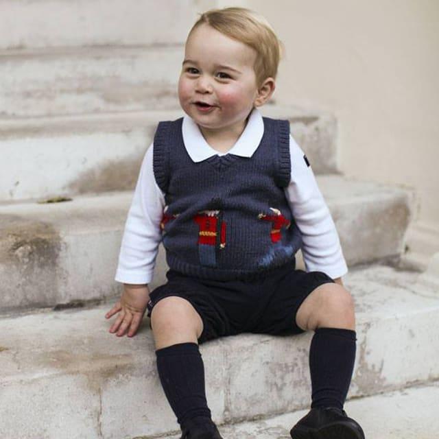 Prinz George in kurzen Hosen auf einer Steintreppe sitzend und lachend.