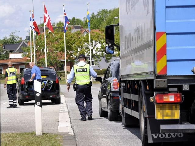 Dänische Beamte in Signalwesten kontrollieren Fahrzeuge am deutsch-dänischen Grenzübergang Pattburg.