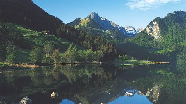 Bild des Schwarzsees mit grünen Hügeln im Hintergrund.