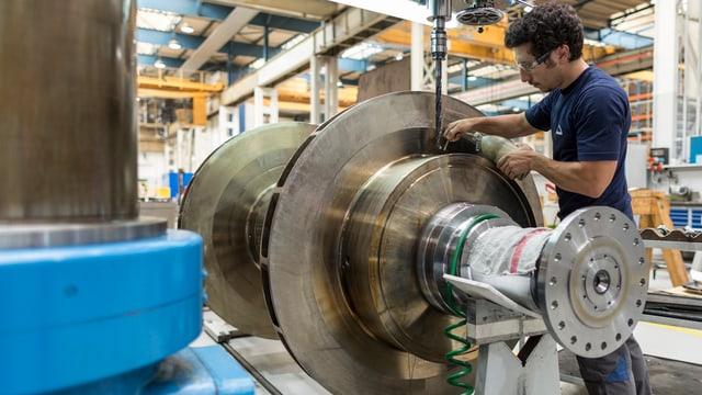 Ein Mann arbeitet an einem grossen Eisenteil.