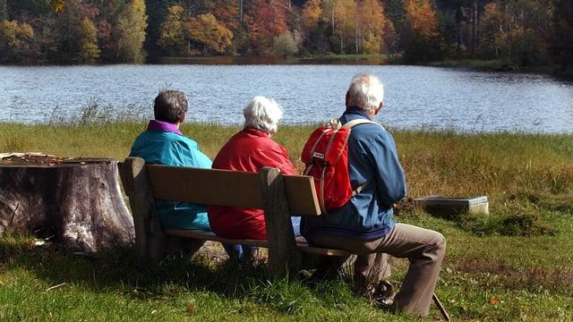 Drei ältere Leute auf einer Bank an einem See