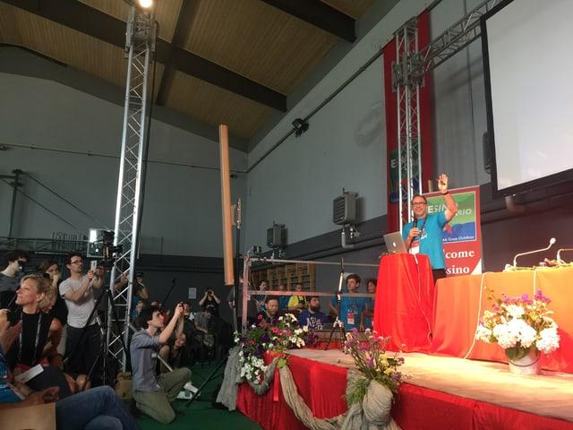 Alle machen ein Foto, die Bühne ist mit Blumenkränzen verziert.