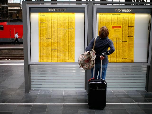 Ein Passagier prüft den Fahrplan auf einem Bahnperron in Frankfurt
