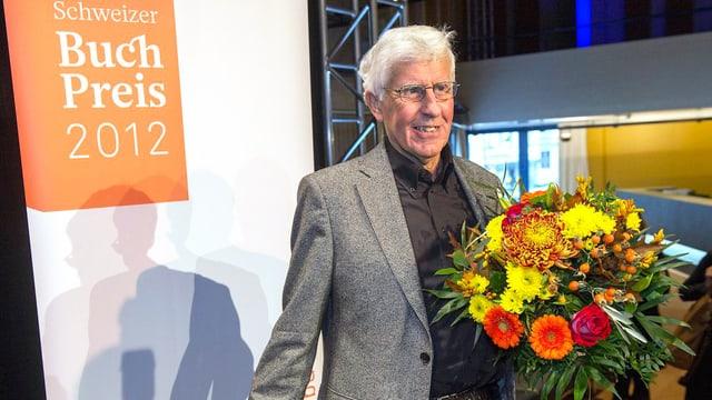 Schweizer Buchpreis-Gewinner Peter von Matt posiert mit einem Blumenstrauss in der Hand.