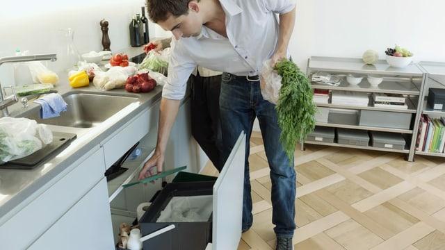 Ein Mann öffnet den Grünabfall-Behälter in der Küche.