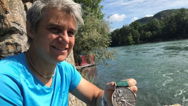 Sabine Eichenberger zeigt eine Medaille, im Hintergrund die Aare