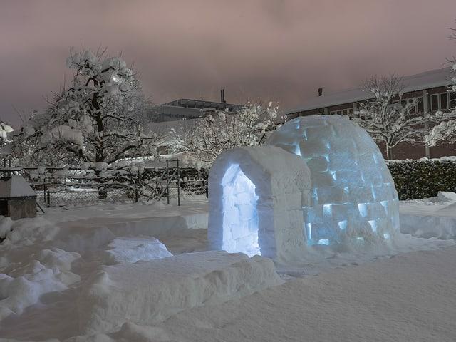 Iglu in einem Garten beleuchtet am Abend mit viel Schnee