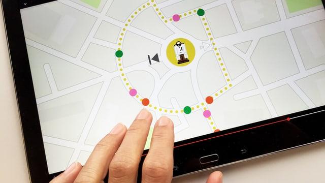Hand vor einem Tablet. Auf dem Tablet eine Stadtkarte, in der Mitte die grafische Darstellung eines Mannes mit Bart.