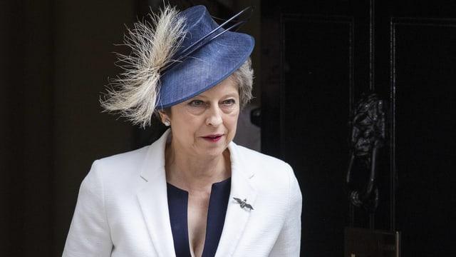 May in weissem Blazer mit auffäligem, blauem Hut.