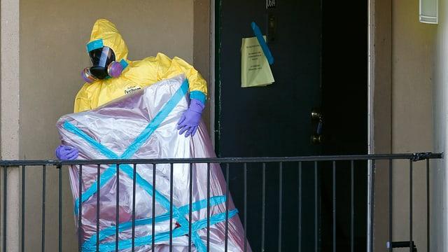 Mann mit Schutzanzug trägt Gegenstand aus Ebola-verseuchter Wohnung hinaus