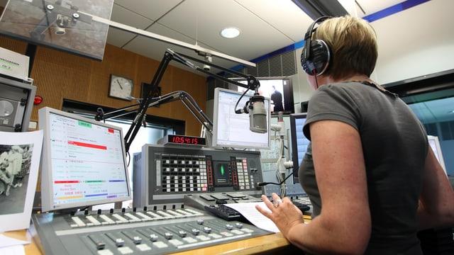 Eine Frau mit Kopfhörern von hinten am Regiepult sitzend.