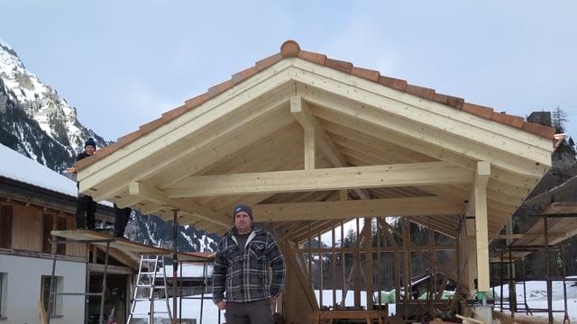 Mann vor Holzhaus im Bau