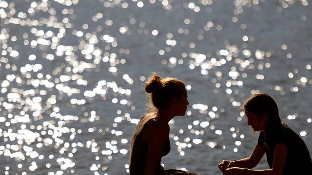Zwei junge Frauen am Zürichsee, der im Sonnenlicht glitzert.