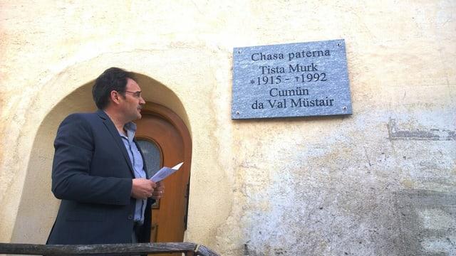 Arno Lamprecht, il president communal da la Val Müstair, guarda sin la tavla ch'è vegnida inaugurada a chaschun da la festa da commemoraziun.