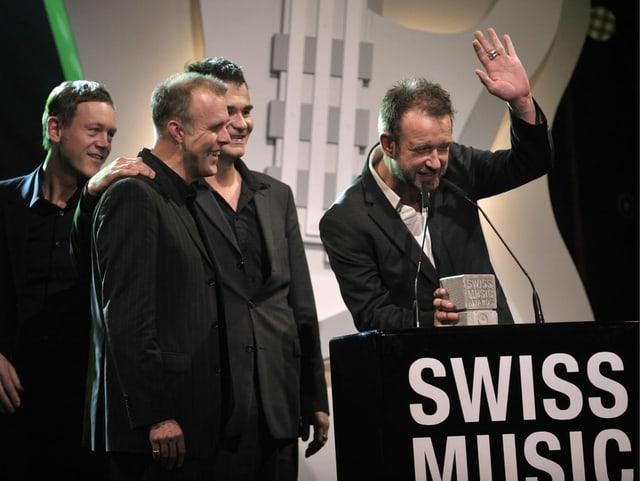 Drei Männer stehen hinter einem Podium und sprechen ins Mikrophon.