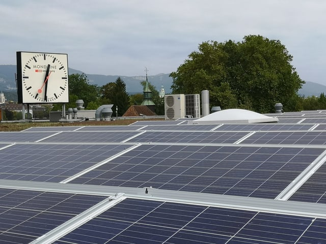 Solaranlage auf einem Flachdach. Dahinter eine grosse Uhr.