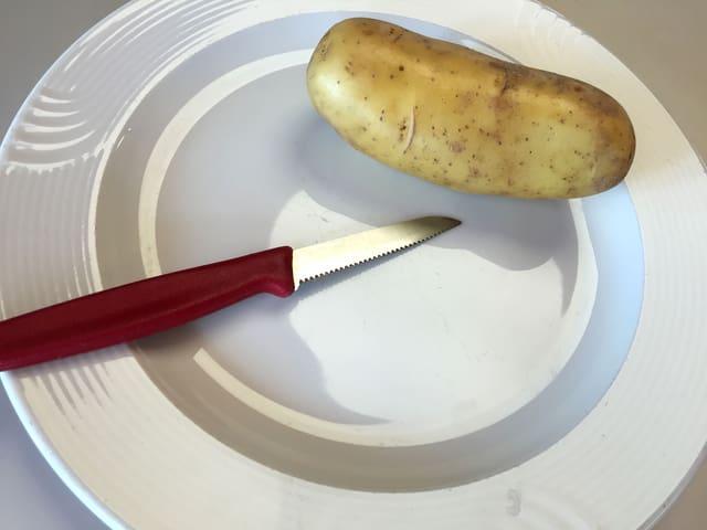 Kartoffel und Messer auf Schnittbrett.