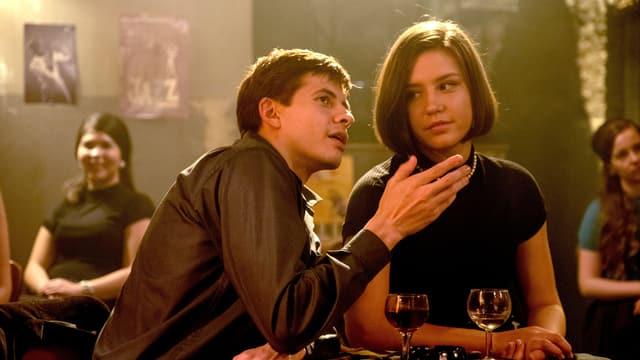 Ein junger Mann und eine junge Frau unterhalten sich in einem Lokal an einem Tisch.