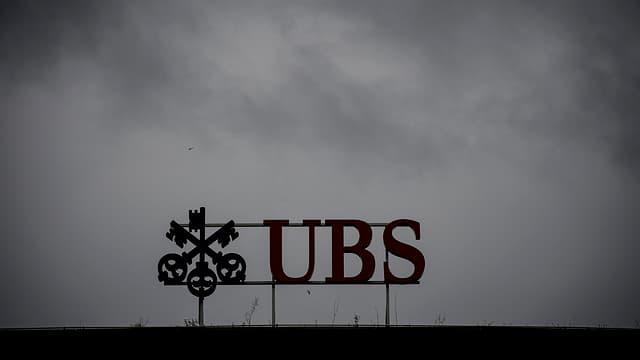 UBS-Logo vor bewölktem Himmel.
