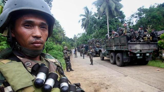Soldaten in einem Lastwagen, einer mit Munition davor.