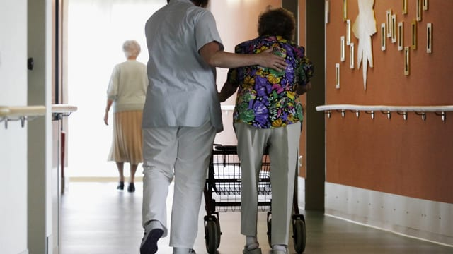 Pflegerin begleitet alte Frau im Gang.