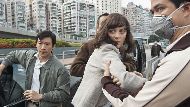 Eine Frau wird von asiatischen Männern verschleppt.
