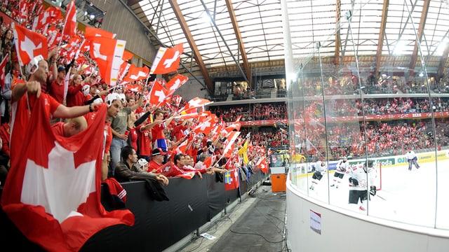 Das Publikum schwenkt Schweizer Fahnen bei einem Eishockey-Match.