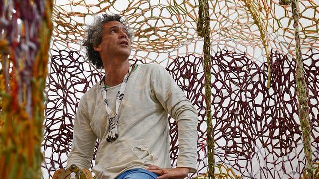Ernesto Neto sitzt vor einem gehäkelten Netz.