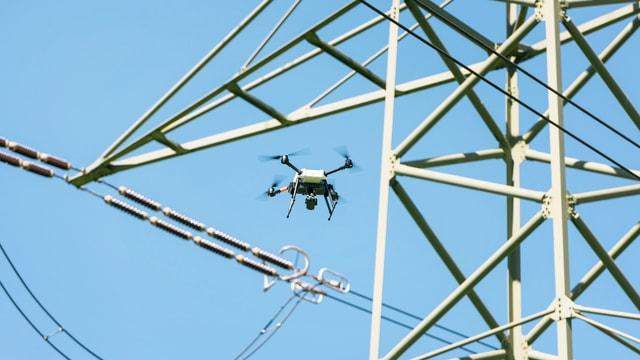Drohne neben einem Hochspannungsmast