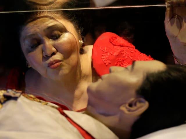 Imelda Marcos küsst ihren toten Ehemann Ferdinand durch die Glasscheibe des Sarkophags mit dem konservierten Leichnam von Marcos.