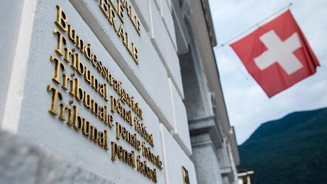Schriftzug and Hauswand, im Hintergrund ist eine Schweizer Fahne erkennbar.