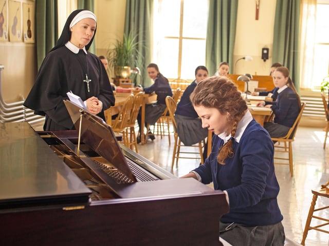 Eine Nonne steht neben einem Klavier. Ein Mädchen spielt Klavier.