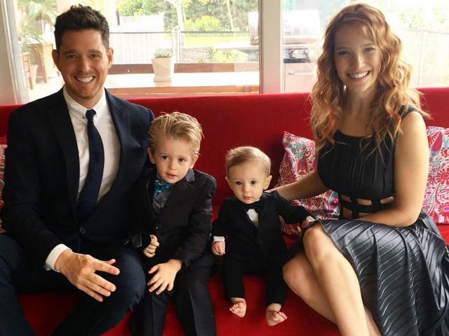 Familie in festlicher Kleidung auf rotem Sofa
