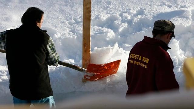Männer schaufen Schnee an Pfosten.