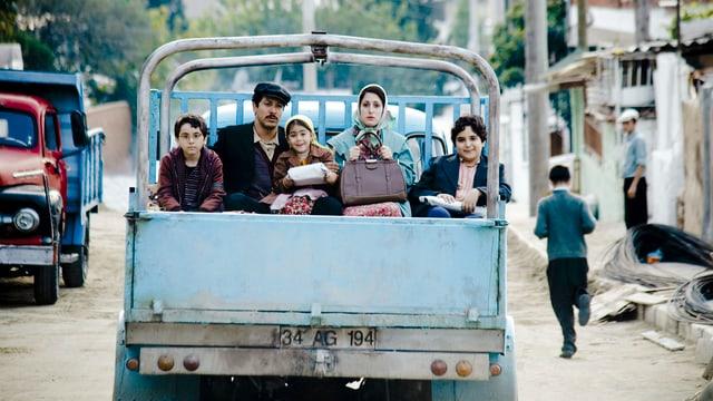 Eine Familie sitzt hinten auf einem Lastwagen.