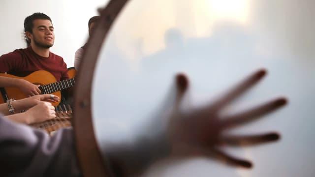Eine Hand liegt auf einem Tamburin. Im Hintergrund lehnt ein Mann an der Wand und spielt Gitarre.