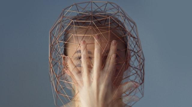 Eine Frau  mit einem Stahldraht vor dem Kopf.