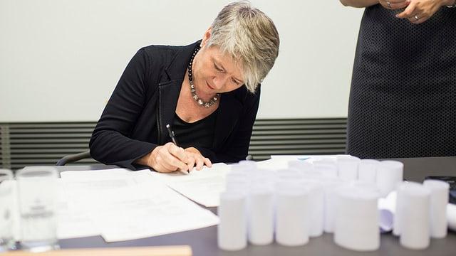 Jacqueline Fehr setzt ihre Unterschrift auf ein Dokument, vor ihr auf dem Tisch stehen die aufgerollten Nationalratslisten.