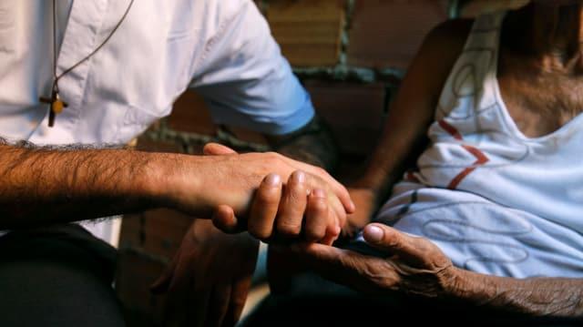 Ein Mann mit Christus-Kreuz-Halskette reicht einer anderen Person die Hand