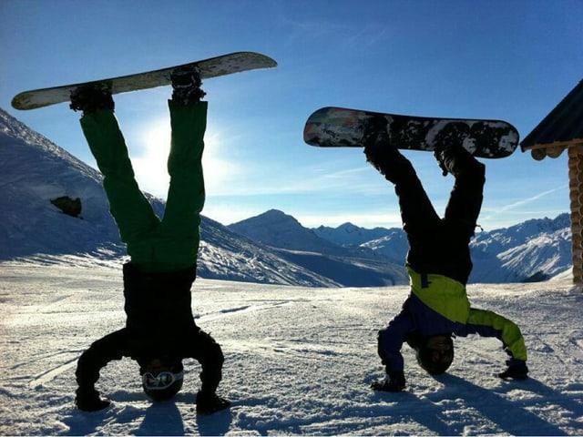 Zwei Snowboarder im Handstand.