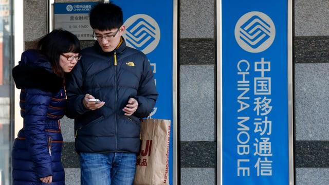 Eine Chinesin und ein Chinese stehen vor zwei China Mobile-Plakaten und schauen auf ein iPhone.
