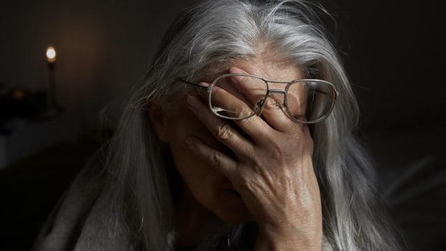 Symbolbild: Grauhaarige Frau hält die Hand vors Gesicht - aus Verzweiflung.