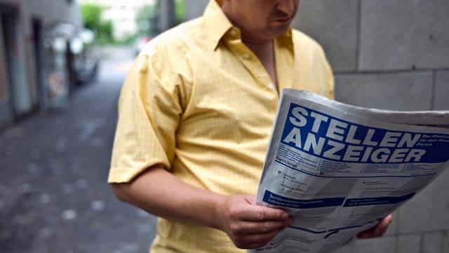 Ein Arbeitsloser Mann studiert in Zürich den Stellenanzeiger
