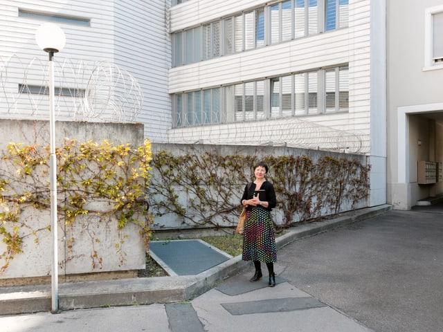 Eine Frau mit gepunktetem Rock steht vor einer Betonwand, welche mit einem Stacheldrathzaun versehen ist.