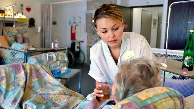 Eine Pflegerin gibt einer Patientin ein Glas Tee zum Trinken.